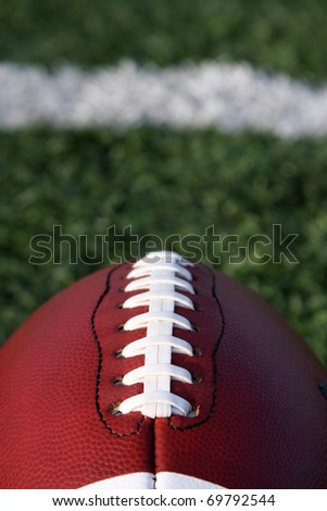 American Football close up with yard line and copy space beyond - stock photo