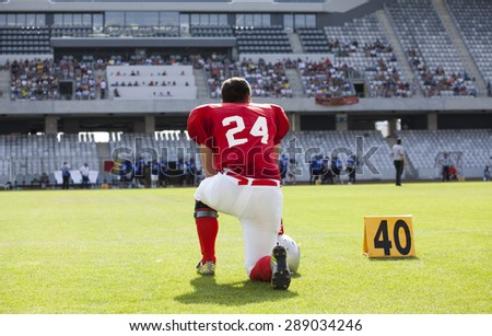 American football game. Out of focus players in the background - stock photo