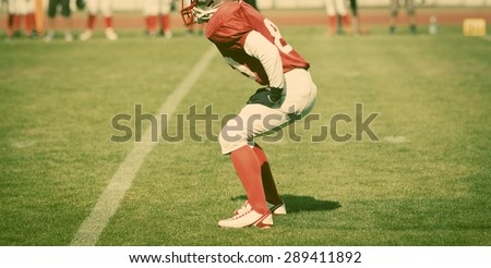 american football game with out of focus players in the background - sports concept, retro style photo - stock photo