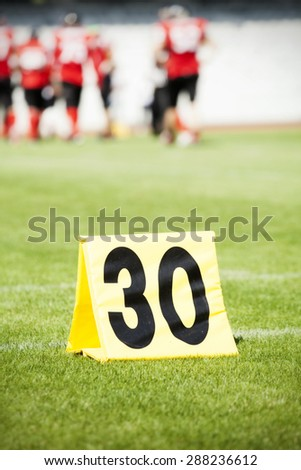 American football game. Yard markers with out of focus players in the background