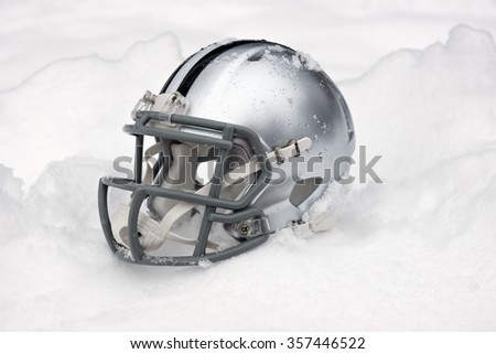 american football helmet covered in the snow and ice - stock photo