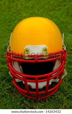 American football helmet in grass - stock photo