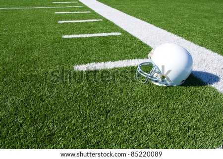 American Football Helmet on the Field with yard lines beyond - stock photo