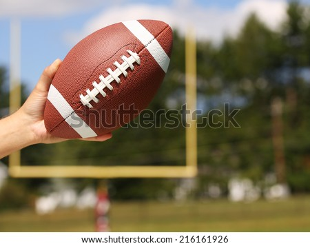 American Football in Hand over Field with Goal Post or Uprights