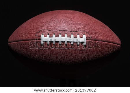 american football in shadows with seams facing front - stock photo