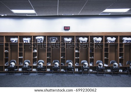 American Football Locker Room In A Large Stadium. Helmets Sitting On Chairs  And Jersey`
