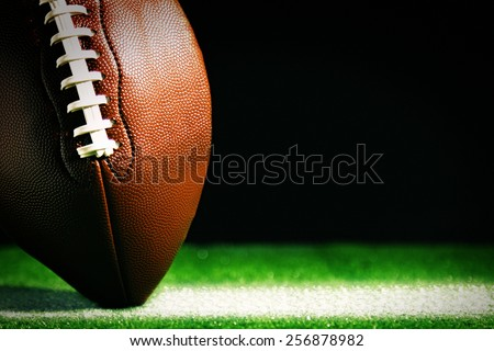 American football on green grass, on black background - stock photo