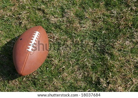 American football on rough grass - stock photo