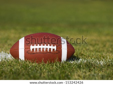 American Football on the field with yard line and green grass  - stock photo