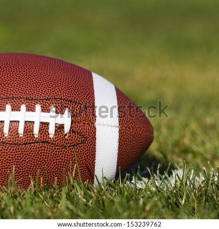 American Football on the field with yard line and green grass. Closeup - stock photo