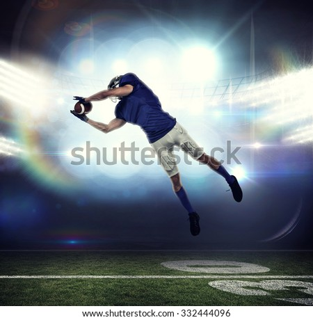 American football player catching ball in mid-air against american football arena - stock photo