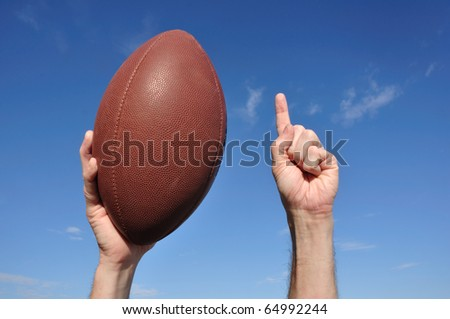 American Football Player Celebrates a Touchdown Holding a American Football and Giving a Number One Sign - stock photo