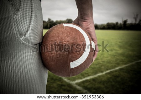 American football player holding ball against empty rugby pitch - stock photo