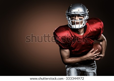 American football player holding ball against orange background with vignette - stock photo