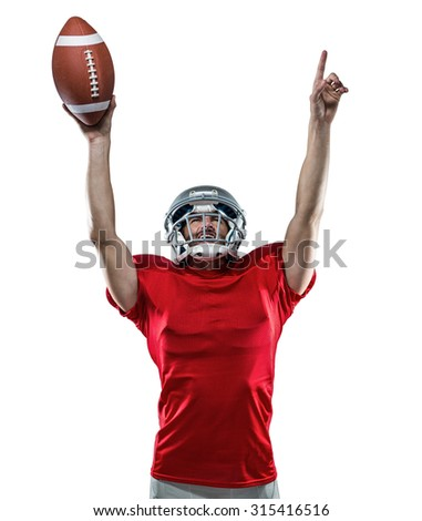 American football player holding ball with arms raised standing against white background - stock photo