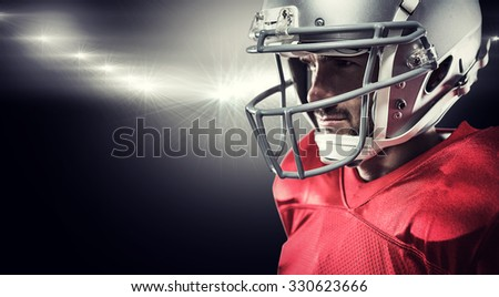 American football player in red jersey looking away against spotlight