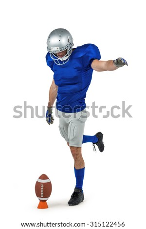 American football player kicking ball against white background