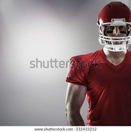 American football player looking at camera against grey background