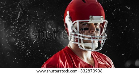 American football player looking at camera against rain