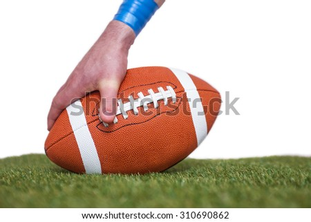 American football player placing the ball on the grass over a white background