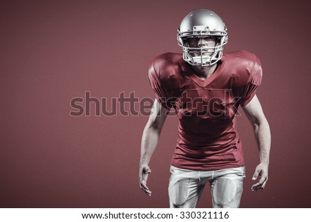 American football player standing in position against red