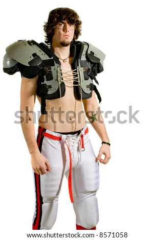 American football player. Standing shirtless with shoulder pads.