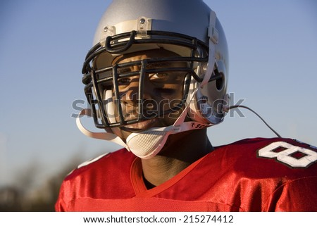 American football player wearing red football strip and protective helmet, close-up, portrait - stock photo
