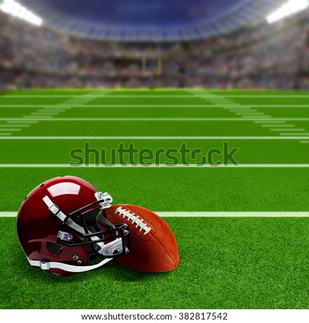 American football stadium full of fans with football helmet and ball on the field. Deliberate focus on equipment and shallow depth of field on background. Floodlights flare for effect and copy space.