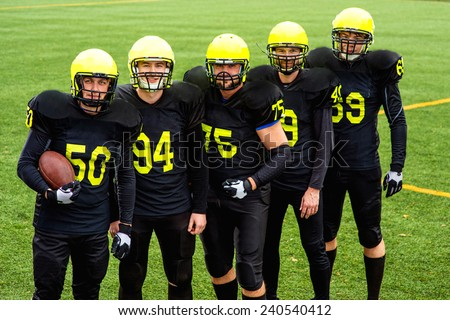 American football team in sportswear with the ball standing together on the sports ground - stock photo