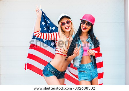 American girls. Two playful young women gesturing peace sign and holding American flag while standing against the garage door - stock photo