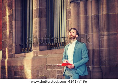 American Graduate Student with beard, mustache studying in New York, wearing cadet blue suit, standing against wall with windows on campus, reading red book, thinking. Instagram filtered effect.  - stock photo