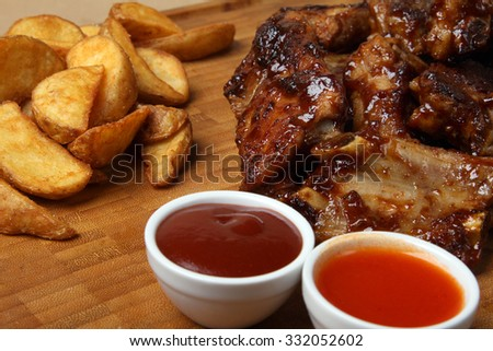 American grilled ribs on the grill topped with barbecue sauce with onion rings and hot crispy potatoes - American food - fast food - stock photo