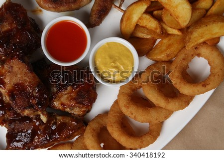 American grilled ribs on the grill topped with barbecue sauce with onion rings and hot crispy potatoes -, chicken wings in teriyaki sauce, American food - fast food - stock photo