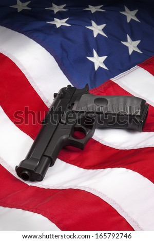 American Gun Law - Hand Gun on the flag of the United States of America. - stock photo
