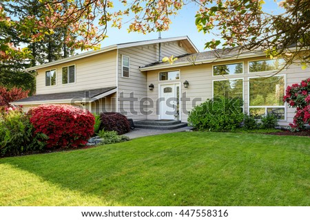 American home with well kept lawn and flowers. Enterance to the house - stock photo