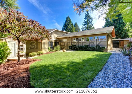 American house exterior. Cozy backyard with small shed, green lawn and stone walkway - stock photo