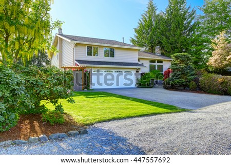 American house with beautiful curb appeal. View of car garage and driveway