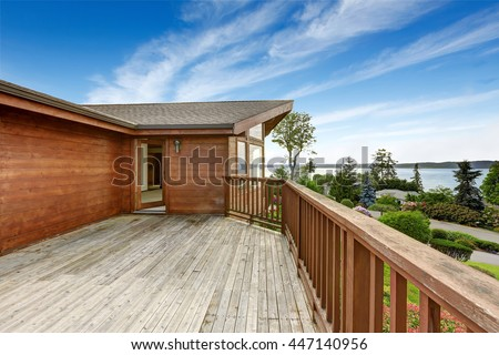 American house with wooden walkout deck overlooking backyard and ocean - stock photo