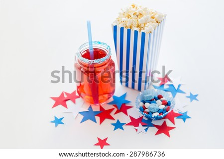american independence day, celebration, patriotism and holidays concept - close up of juice glass or mason jar, popcorn and candies with stars confetti decoration at 4th july party - stock photo