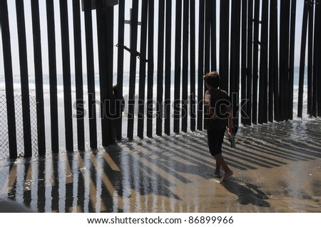 American kid meets mexican kid on the other side of the fence. USA Mexico Border, San Diego Tijuana. - stock photo