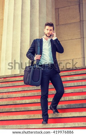 American man with beard traveling, working in New York, wearing black suit, white shirt, shoulder carrying travel bag / briefcase, talking on cell phone, walking down stairs. Instagram filtered effect - stock photo