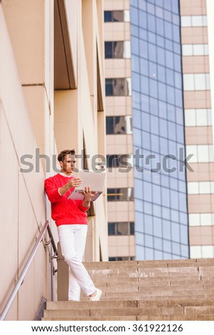 American Man working remotely. Young blonde professional, wearing red knit sweater, white pants, reading, working on laptop computer, standing against wall outside office building in New York.   - stock photo