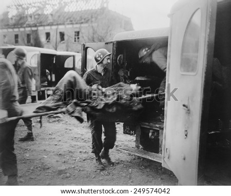 American medics place an almost-dead German slave laborer in an ambulance at Nordhausen. U.S. 3rd Army liberated the camp on April 12, 1945. Germany, World War 2. - stock photo