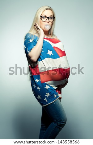 American Mom Concept: Surpised young pregnant woman in american flag like dress and trendy glasses chewing bubble gum over gray background. Hipster style. Studio shot