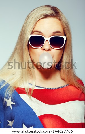 American Mom Concept: Young pregnant woman in american flag like dress and trendy sunglasses chewing bubble gum and posing over gray background. Hipster style. Close up. Studio shot - stock photo