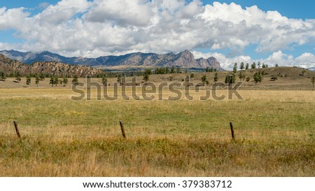 American mountains farmland with cow herd grazing on dry grass with cloudy blue sky
