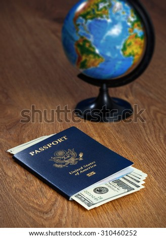 American passport with dollars and the globe - stock photo