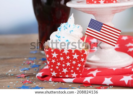 American patriotic holiday cupcake and glass of cola on wooden table - stock photo