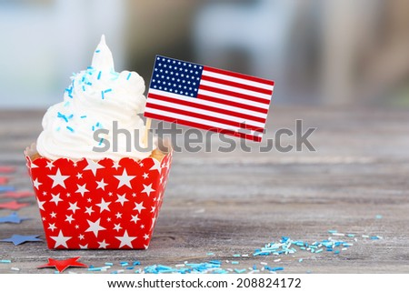 American patriotic holiday cupcake on wooden table - stock photo