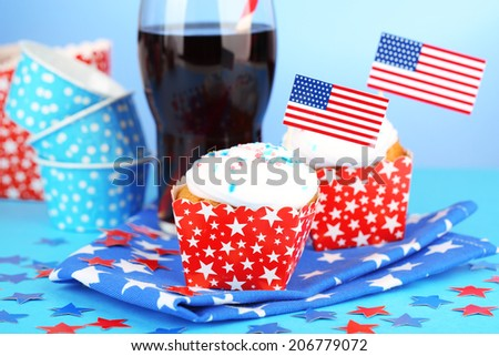 American patriotic holiday cupcakes and glass of cola on blue background